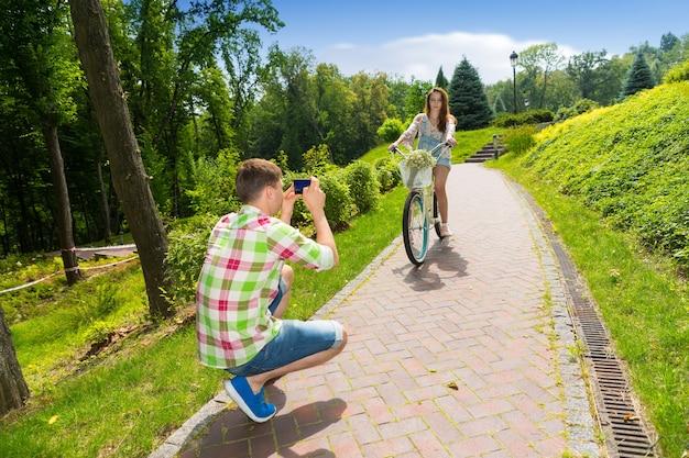 Молодой парень в зелено-красной клетчатой рубашке фотографирует свою девушку, сидящую на велосипеде с букетом маленьких белых цветов в корзине в парке