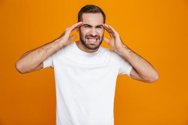 T- 셔츠에 젊은 남자가 비명을 지르고 두통 때문에 사원을 문지르는 동안, 노란색에 고립