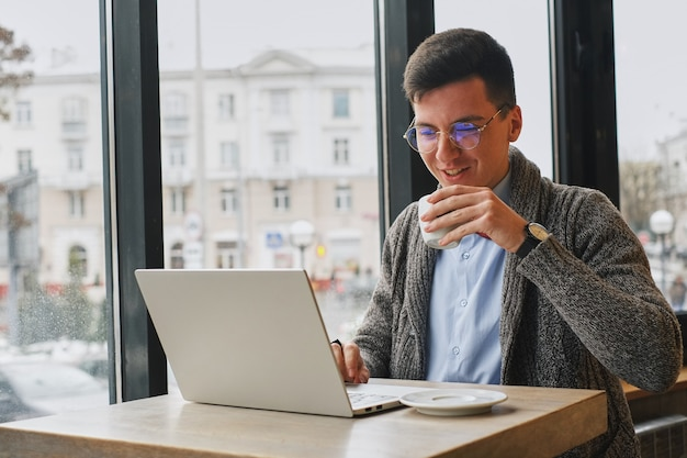 Young guy is freelancer in cafe working behind a laptop