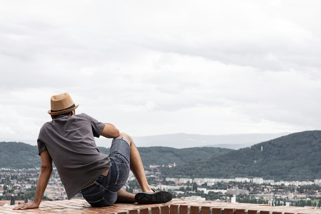 A young guy is sitting on the edge of a tall building and enjoying the view of the mountains