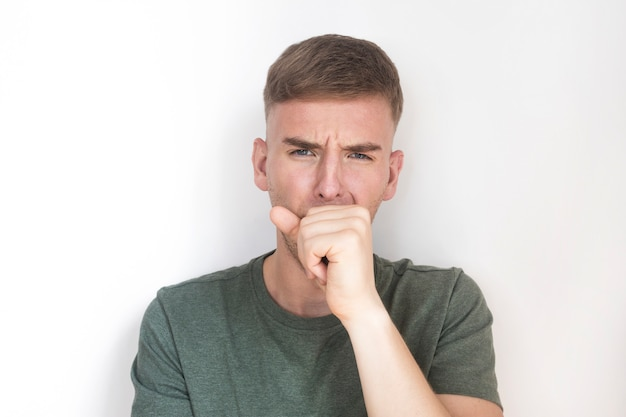 Молодой парень страдает, кашляет в кулак. красивый мужчина имеет симптомы коронавируса, пандемии китайского вируса. загрязнение воздуха. ncov 2019. больной человек с концепцией кашля.