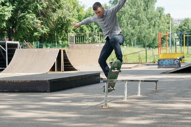 Young guy in jeans and shirt skateboarding on the hedges in sunny summer park