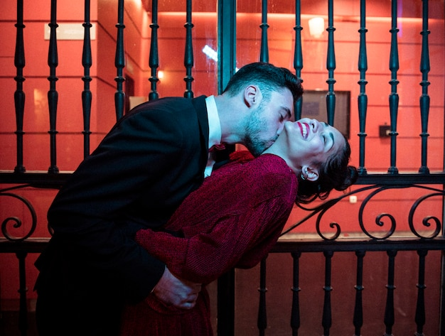 Young guy kissing and bending attractive cheerful lady near gates