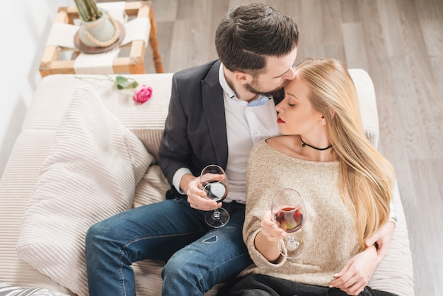 Young guy kissing in front of lady with glasses of wine and sitting on sofa in room