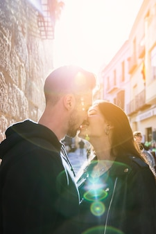 Young guy kissing happy lady on street