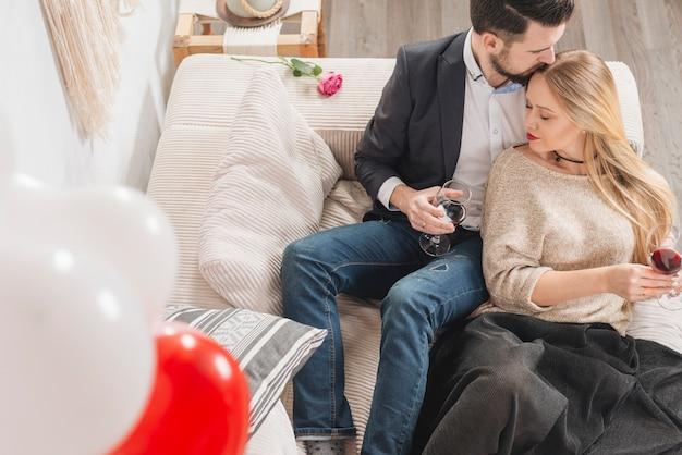 Молодой парень целуется перед дамой с бокалами вина на диване возле воздушных шаров в комнате