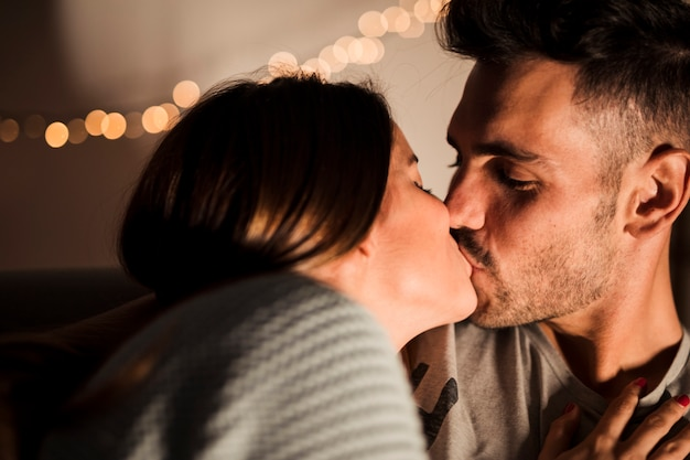 Young guy kissing with lady near fairy lights