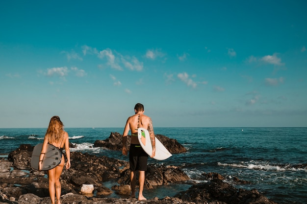 Young guy and lady with surf boards going on stone shore to water