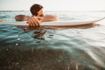 Young guy lying on surf board in water