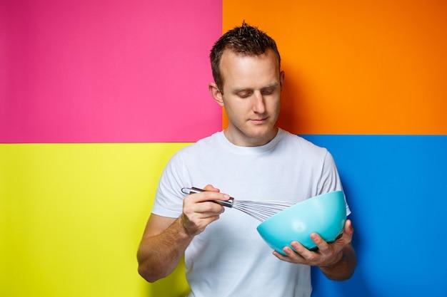 白いtシャツ、カラフルな背景、台所用品、料理人、感情の写真の若い男の男