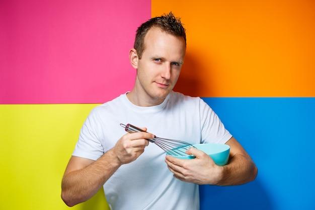 흰색 티셔츠를 입은 젊은 남자, 화려한 배경, 주방 용품, 요리사, 감정 사진