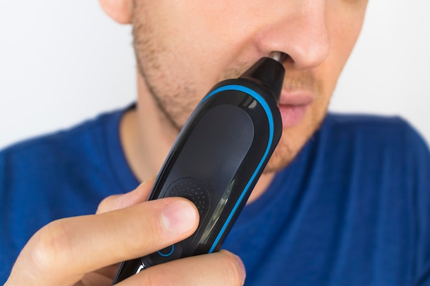 Young guy, man using an electric razor to remove excess nose hair. close up photo. taking care of eauty, hair skin care. removing hair with trimmer. unrecognizable person, male. personal hygiene.