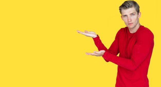 黄色の背景にヨーロッパの外観の若い男。 2つの空の手のひらを開いたままにします。コピースペース