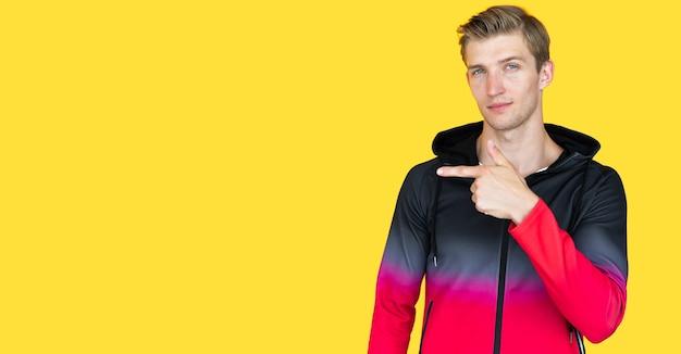 黄色の背景にヨーロッパの外観の若い男。空の場所に指を向けます。コピースペース