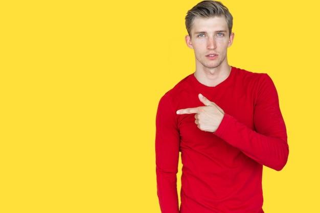 黄色の背景にヨーロッパの外観の若い男。人差し指は空のスペースを指しています。コピースペース