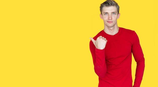 黄色の背景にヨーロッパの外観の若い男。親指は空のスペースを指しています。コピースペース