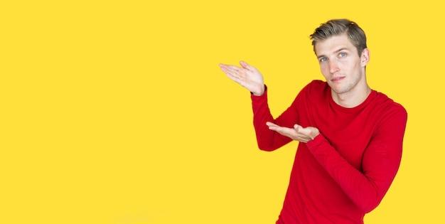 黄色の背景にヨーロッパの外観の若い男。 2つの空の開いた手のひら