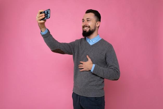 Молодой парень на розовом фоне делает селфи