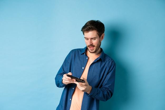 젊은 남자가 휴대 전화에서 비디오 게임을하고, 몸을 기울이고 스마트 폰을 수평으로 들고 파란색 배경에 서 있습니다.