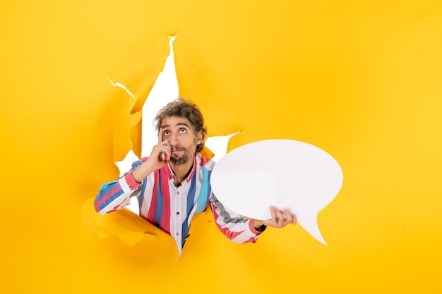 Young guy pointing white page with free space and thinking deeply in a torn hole in yellow paper