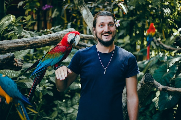 Young guy posing in a zoo with a parrot in his hand, a bearded man and a bird