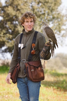 Young guy practicing falconry with a beautiful specimen of goshawk