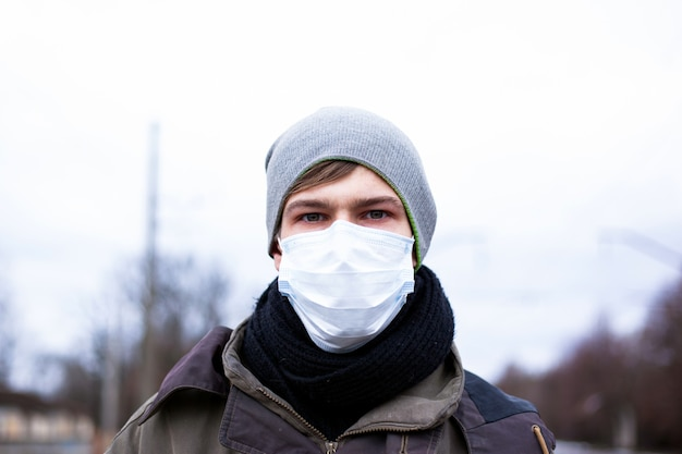 A young guy in a protective mask protects himself from coronavirus, a pandemic of the chinese virus. ncov-2019.