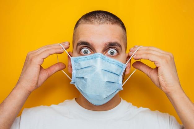 若い男は医療用マスクを着用します。黄色の一般的な風邪やインフルエンザのウイルス性疾患の予防。コロナウイルスとcovid-19のコンセプト。