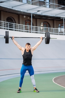 Young guy raises the bar in the stadium, outdoor workout