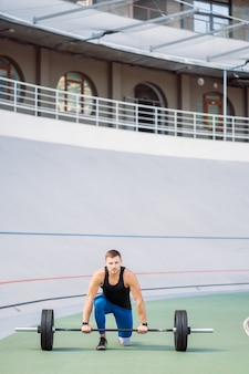 若い男がスタジアム、屋外トレーニングでバーを上げる