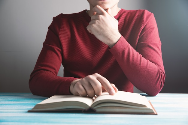 Young guy reading a book on the table