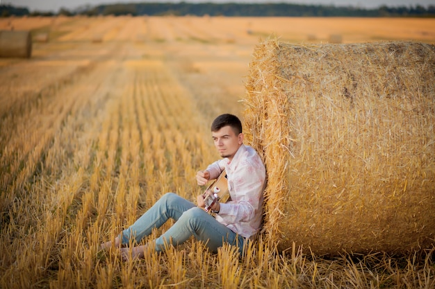 Молодой парень, отдыхая в сельской местности во время игры на гитаре