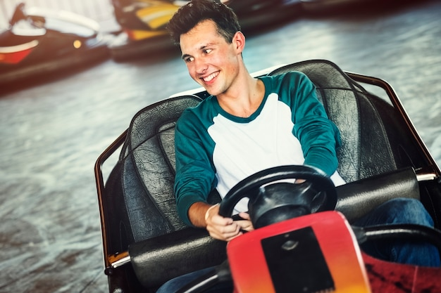 Young guy riding the bumper cars at an amusement park