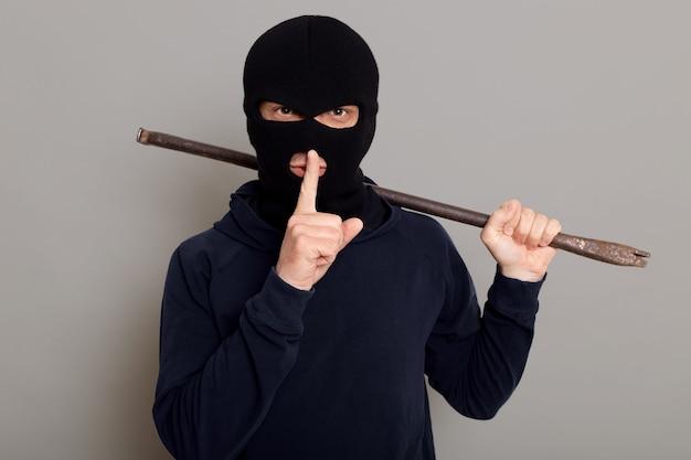 Молодой парень грабитель, одетый в черную толстовку с маской на лице