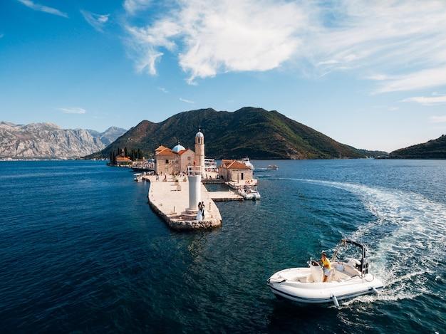 화창한 여름 날에 바다에서 보트를 타고 항해하는 젊은 남자 신부와 신랑은 부두에 서