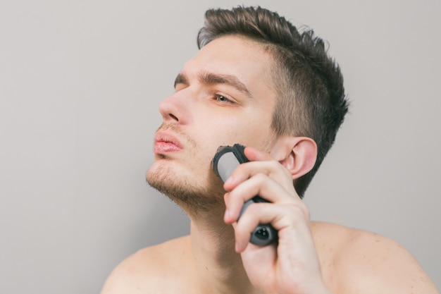 Young guy shaves with an electric razor