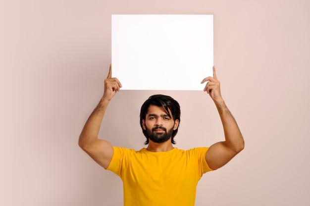 Молодой парень показывает пустой белый плакат вывески