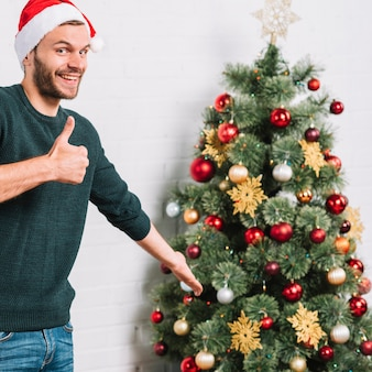 Young guy showing good near Christmas tree