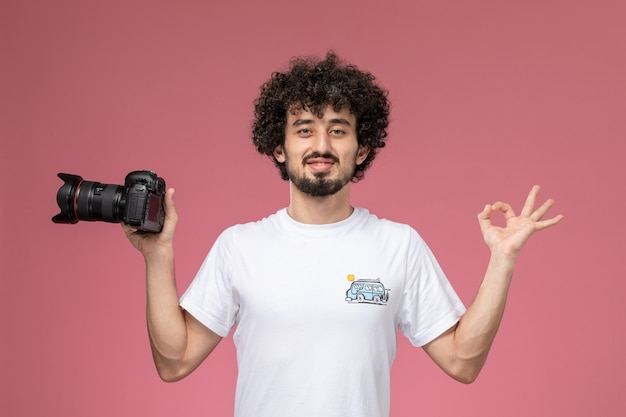 Young guy showing okay gesture and holding photocamera