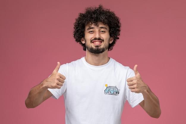 Giovane ragazzo che mostra i pollici in su con la maglietta bianca