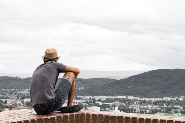 A young guy sit on the edge of a tall building and looks into the distance towards the mountains