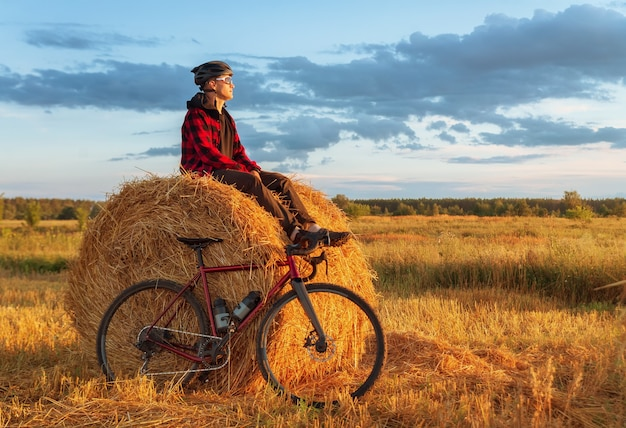 若い男は夜明けにフィールドで自転車と干し草の山に座っています。夕日を楽しむフィールドのサイクリスト。