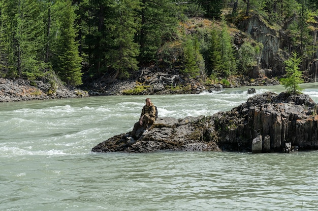 A young guy sits on a rock in the middle of a fast mountain river. the traveler rests sitting on a stone by the water