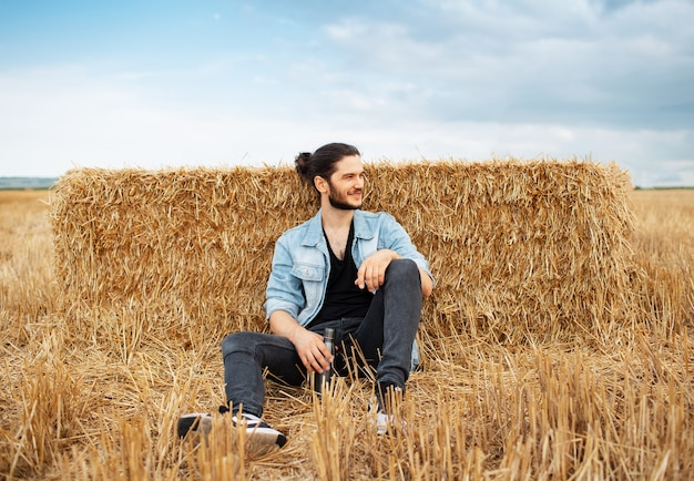 Young guy sitting on background of haystacks in wheat field.