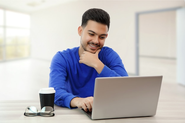 A young guy sitting at a laptop in search of work on the internet , doing business in the global network with a cup of coffee. on light