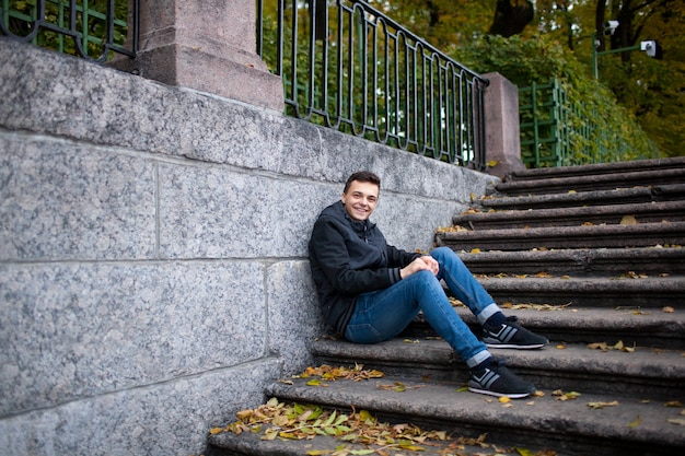 A young guy sitting on the stairs.