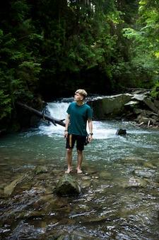 若い男は滝を背景に川のそばに立っています