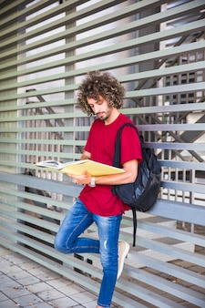 Young guy studying near wall