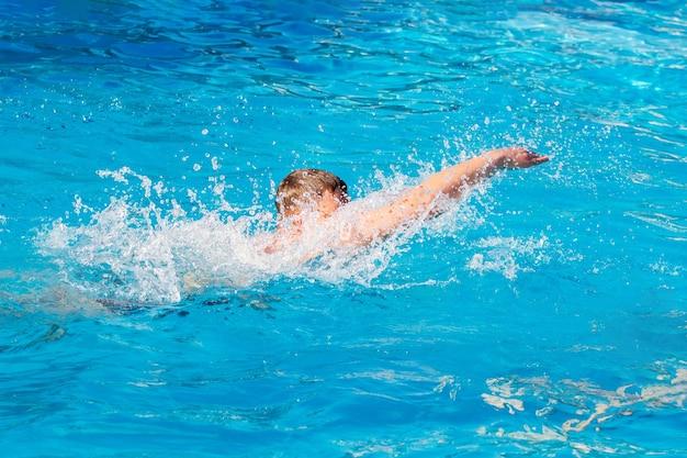 若い男はプールで泳ぎます。リゾートでの夏休み_