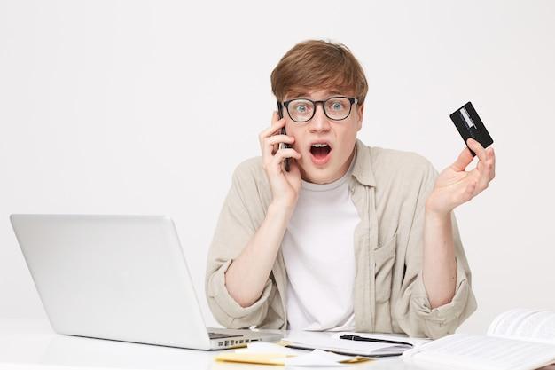 電話で銀行のマネージャーと話している若い男